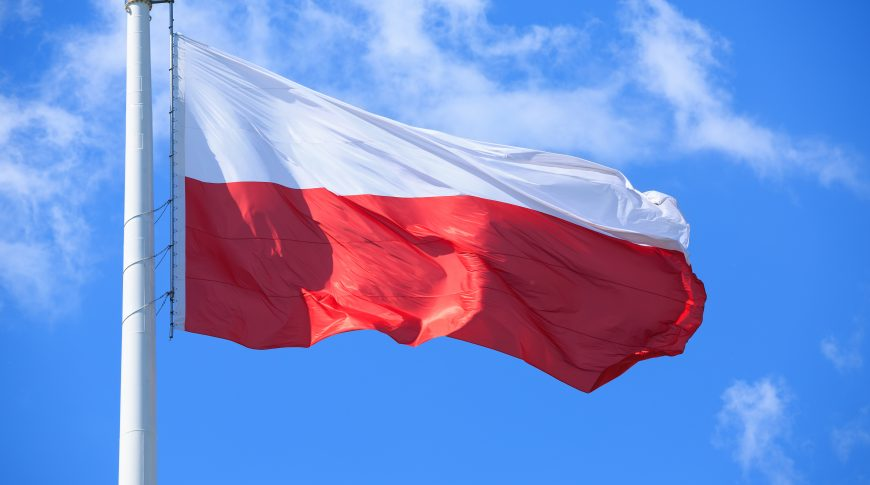 Polish Flag On A Background Of Blue Sky